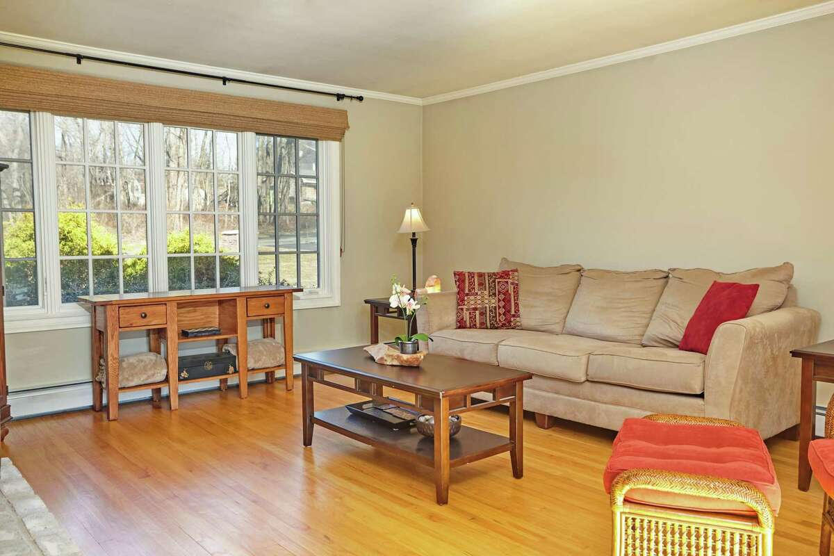 The family room has a floor-to-ceiling white brick fireplace and sliding doors to the patio and pool area.