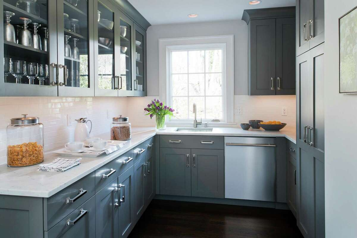 This classically styled butler?'s pantry, designed by Deane Inc. with locations in New Canaan and Stamford, is ideal for entertaining, with its generous counter space, glass-front cabinetry, dishwasher, sink, and even a view!