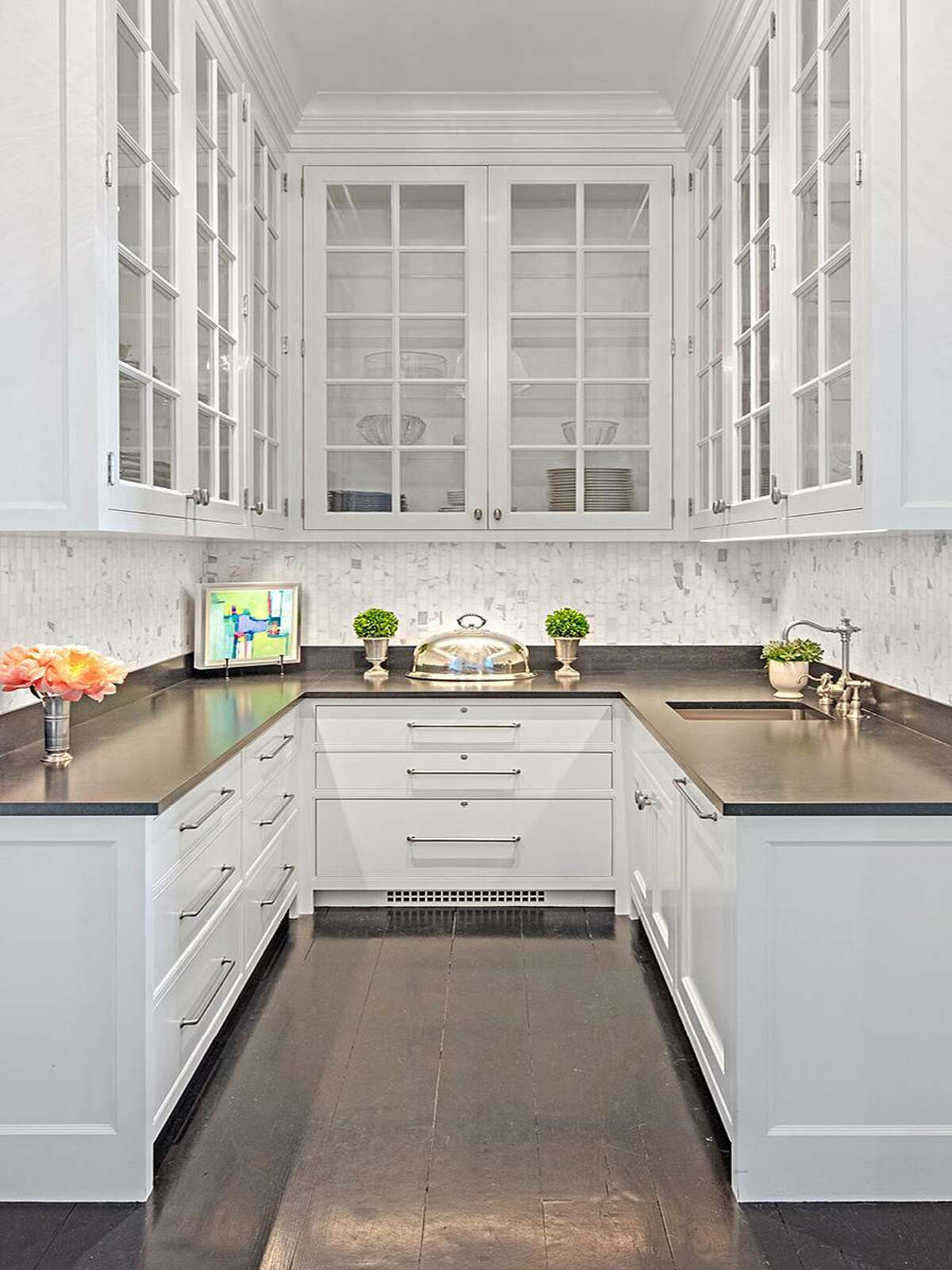 White space: An elegant butler's pantry, with traditional white cabinetry and high ceilings, provides ample space for preparing food and drinks.