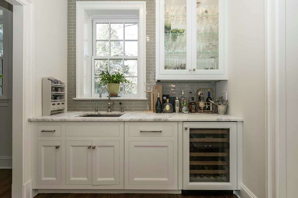 A small space is transformed into a beautiful and efficient butler's pantry, featuring crisp white glass-front cabinetry, marble countertop, glass tile backsplash, wine cooler, and sink...the perfect place to prepare food and drinks, and where the host can hide dirty dishes off while the party is still going on.