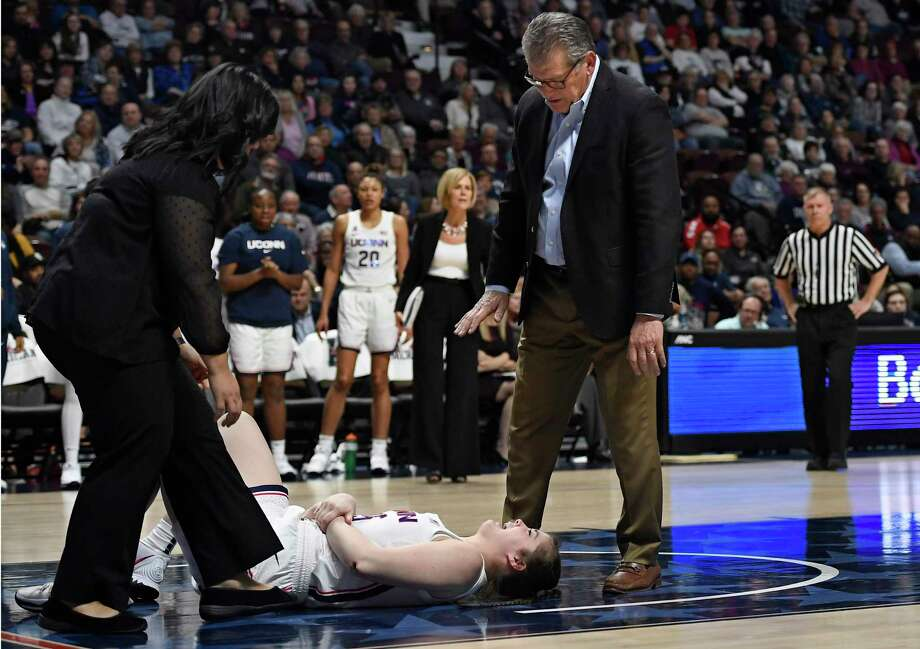 Athletic trainer Janelle Francisco, left, tends to injured player Kyla Irwin as Connecticut head coach Geno Auriemma talks with her during the second half of an NCAA college basketball game in the American Athletic Conference tournament semifinals against South Florida at Mohegan Sun Arena, Sunday, March 8, 2020, in Uncasville, Conn. (AP Photo/Jessica Hill) Photo: Jessica Hill / Associated Press / Copyright 2020 The Associated Press. All rights reserved.