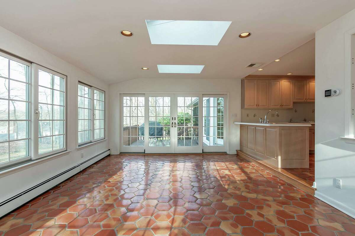 The large sun room off the kitchen has a tile floor in a honeycomb pattern, skylights, and sliding French-style doors to the spacious, raised wood deck and backyard.