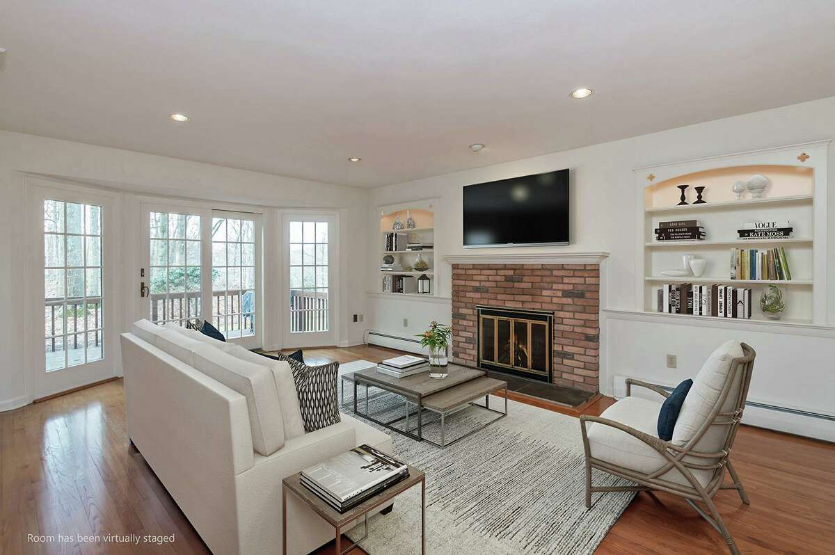 The spacious family room features a brick fireplace flanked by built-in shelving with interior lighting, and sliding doors to the deck. This photo is virtually staged.