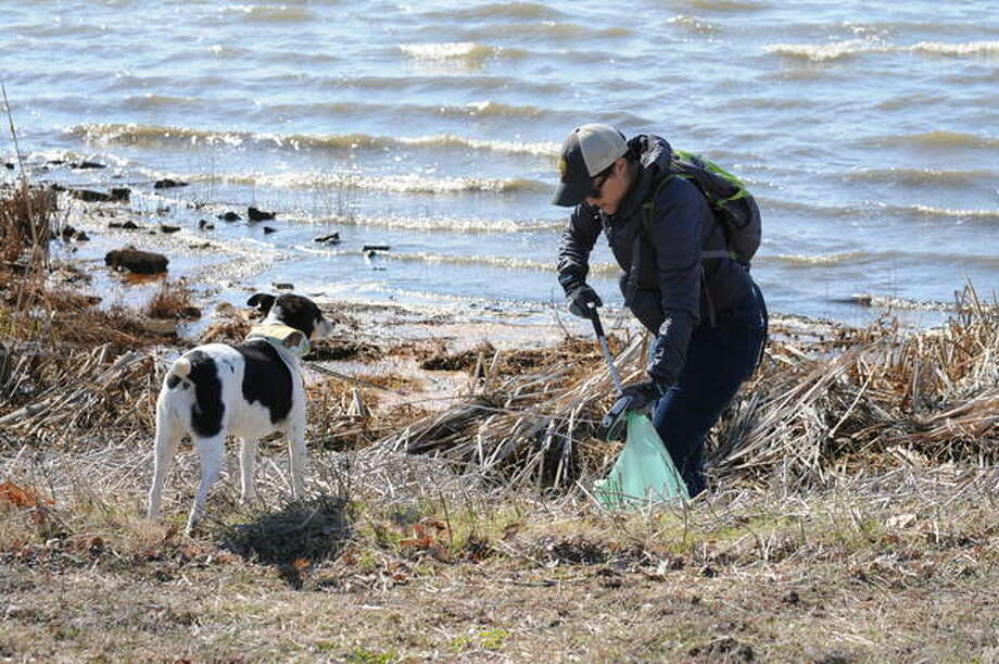 Kallan Virgin of Highland is joined by her dog as she picks up trash on Sunday at Horseshoe Lake State Park at Granite City. More than a dozen volunteers helped clear 40 pounds of trash from the trails, roadways and shoreline.