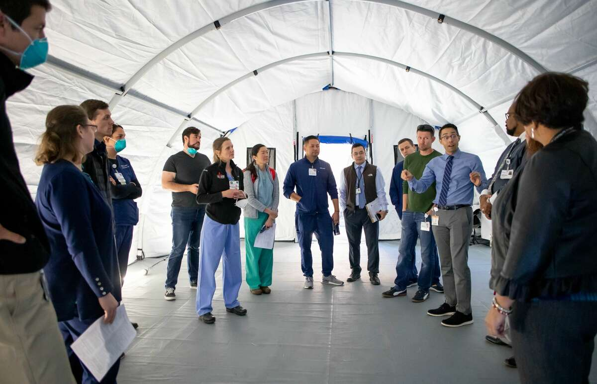 UCSF emergency-medicine physicians, staff and administrators tour one of two mobile emergency rooms installed to treat patients triaged for the coronavirus, outside the emergency department at the Parnassus Heights campus.