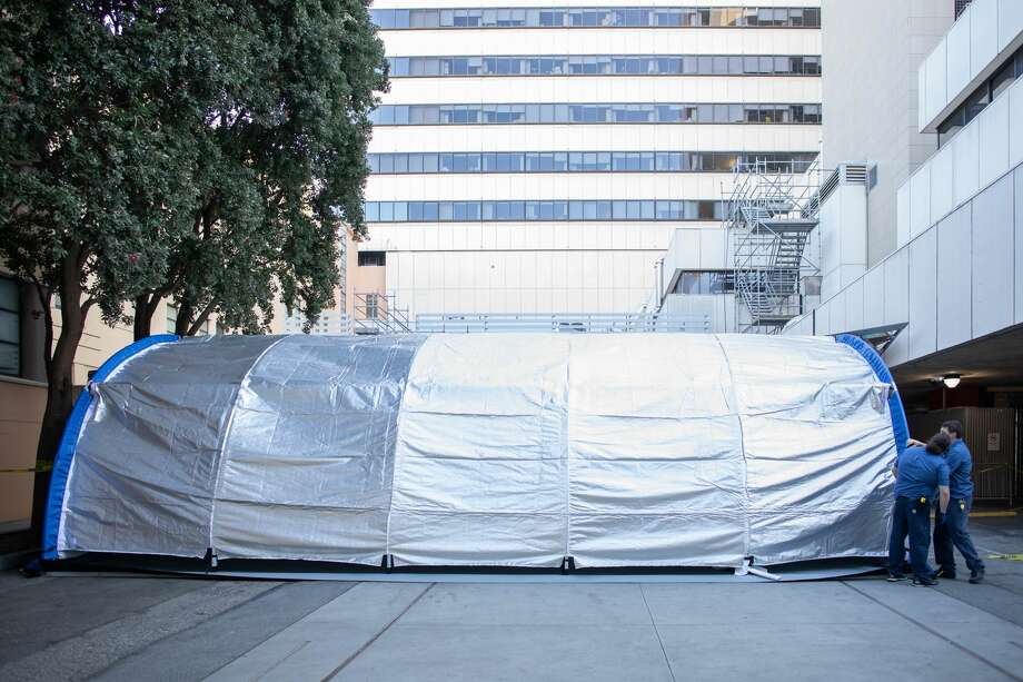 UCSF Facilities Management engineers check the tarp of one of two mobile emergency rooms installed to treat patients triaged for the Coronavirus virus, outside the Emergency Department at the Parnassus Heights campus. Photo: Susan Merrell / UCSF