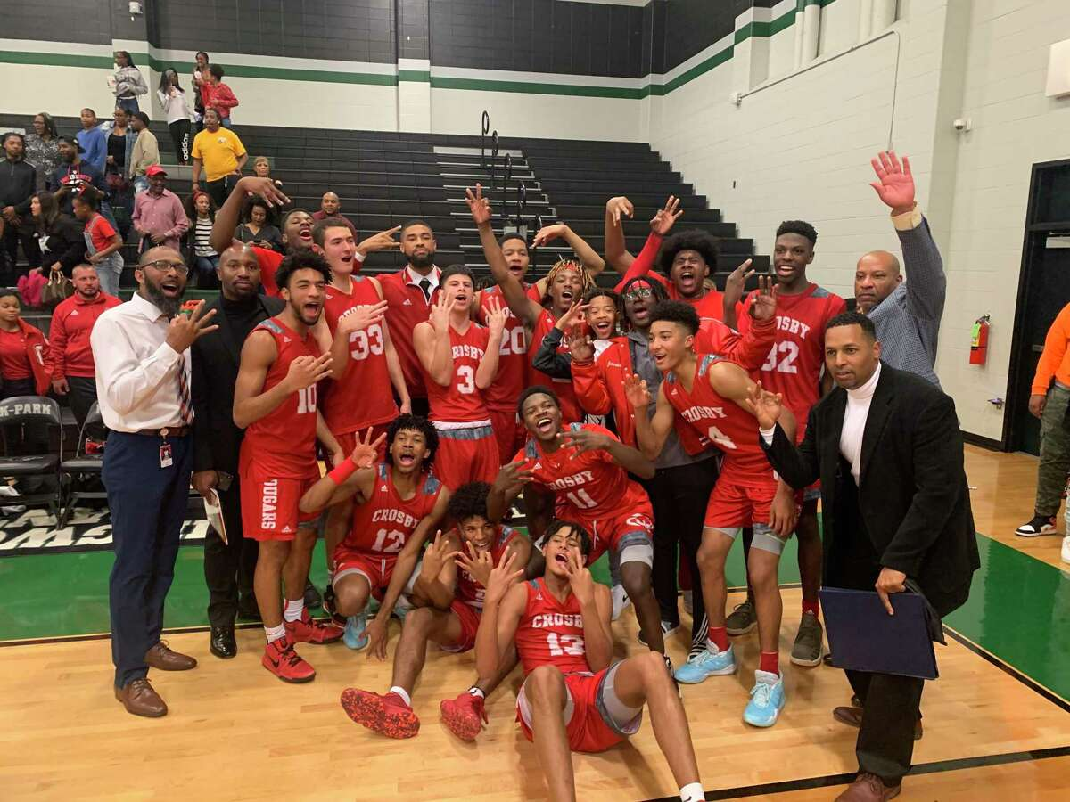 The Crosby Cougar basketball team poses for a picture after beating Northside 79-48 in the area round of the playoffs at Kingwood Park High School on Feb 28. The players hold up three fingers signifying the team's advancing to the third round of the playoffs.