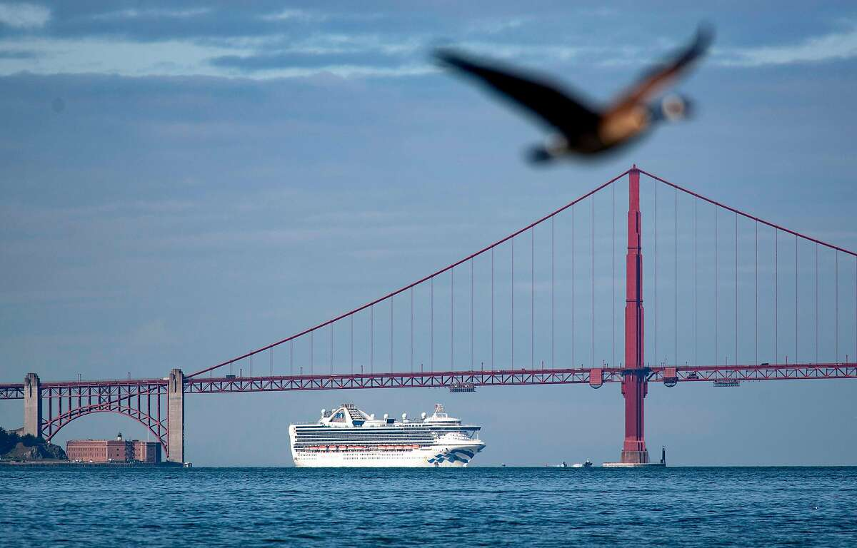 The Grand Princess cruise ship passes under the Golden Gate Bridge as it heads in to shore in San Francisco, California on March 09, 2020. - More than 3,000 passengers are stuck at sea after at least 21 people tested positive for the novel coronavirus (COVID-19) on-board.