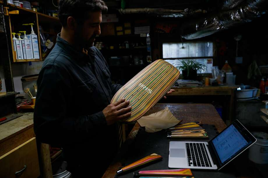 Artist George Rocha shows off a board while packing up an order in his workshop Iris Skateboards on Tuesday, Jan. 21, 2020 in San Francisco, California. He repurposes skateboards to make furniture, skateboards and other objects for his brand Iris Skateboards. Photo: Gabrielle Lurie / The Chronicle