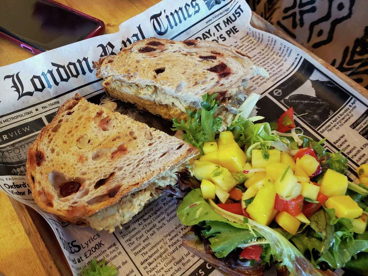 The coronation chicken salad sandwich on housemade cranberry-raisin-walnut bread accompanied by a salad of mango, cukes and tomato on spring greens at Gruel Britannia in Fairfield.