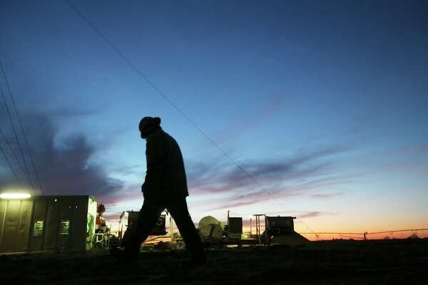 Floorhand Juan Mata, 32, of Alice, Texas walks back to the rig after talking with the toolpusher at the start of the overnight shift at a drilling site in Frio County, Sunday, Jan. 20, 2013.