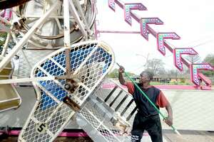 Donald Griffith scrubs one of the seats on The Zipper as carnival workers and vendors continue set-up for Tuesday's opening of the annual Nederland Heritage Festival. Workers throughout the midway were busy scrubbing and hosing down the rides as concern over the spread of coronavirus grows. Photo taken Monday, March 9, 2020 Kim Brent/The Enterprise