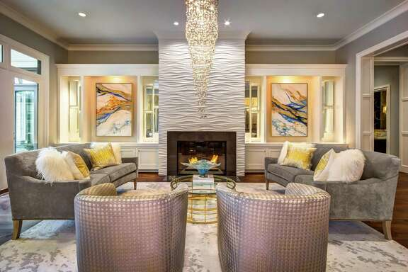 An unusual fireplace treatment in the Bunker Hill home of Brandi and Odeh Khoury involves interlocking panels of gypsum and fibers in a three-dimensional pattern. Art niches are filled with abstract paintings by Cindy Howard, of Decorative and Faux Finishes.