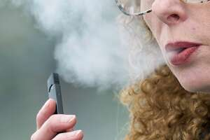 FILE - In this April 16, 2019 file photo, a woman exhales while vaping from a Juul pen e-cigarette in Vancouver, Wash. On Wednesday, Feb. 12, 2020, Massachusetts sued Juul Labs Inc., accusing the company of deliberating targeting young people through its marketing campaigns. (AP Photo/Craig Mitchelldyer, File)