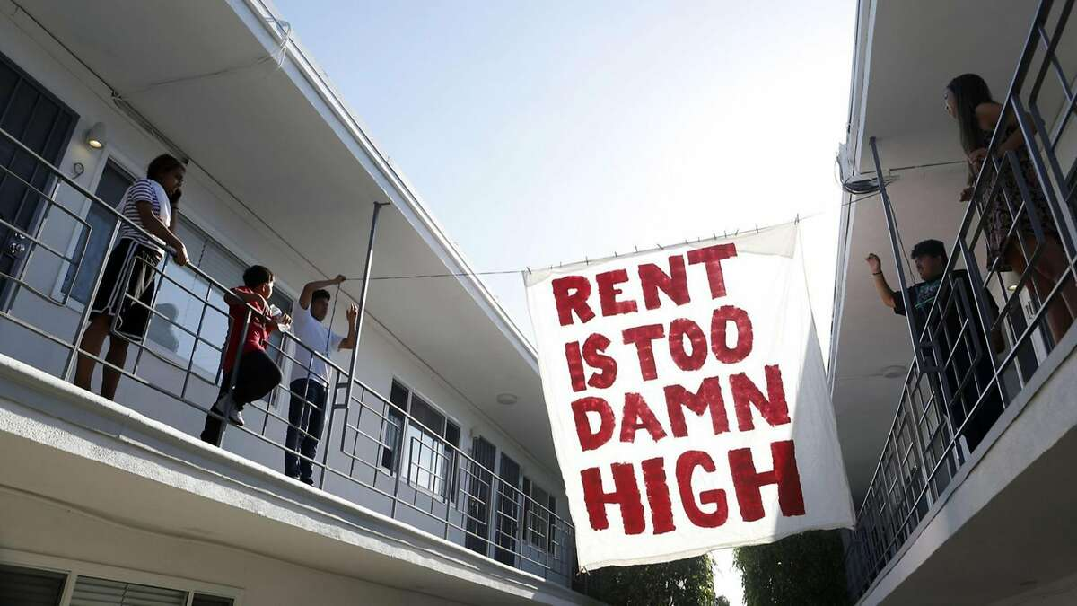Organizers with Housing Long Beach, a local advocacy group pushing for rent control and eviction protections, hangs up a sign in the courtyard of an apartment complex on Cedar Avenue during a movie night they helped put on with tenants on June 15, 2018 in Long Beach, Calif. (Katie Falkenberg/Los Angeles Times/TNS)