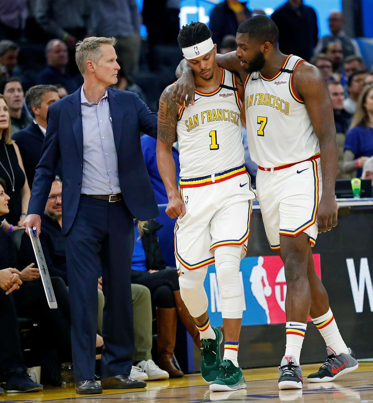 Golden State Warriors' Damion Lee is consoled by Eric Paschall and head coach Steve Kerr in 4th quarter during Toronto Raptors' 121-113 win in NBA game at Chase Center in San Francisco, Calif., on Thursday, March 5, 2020.