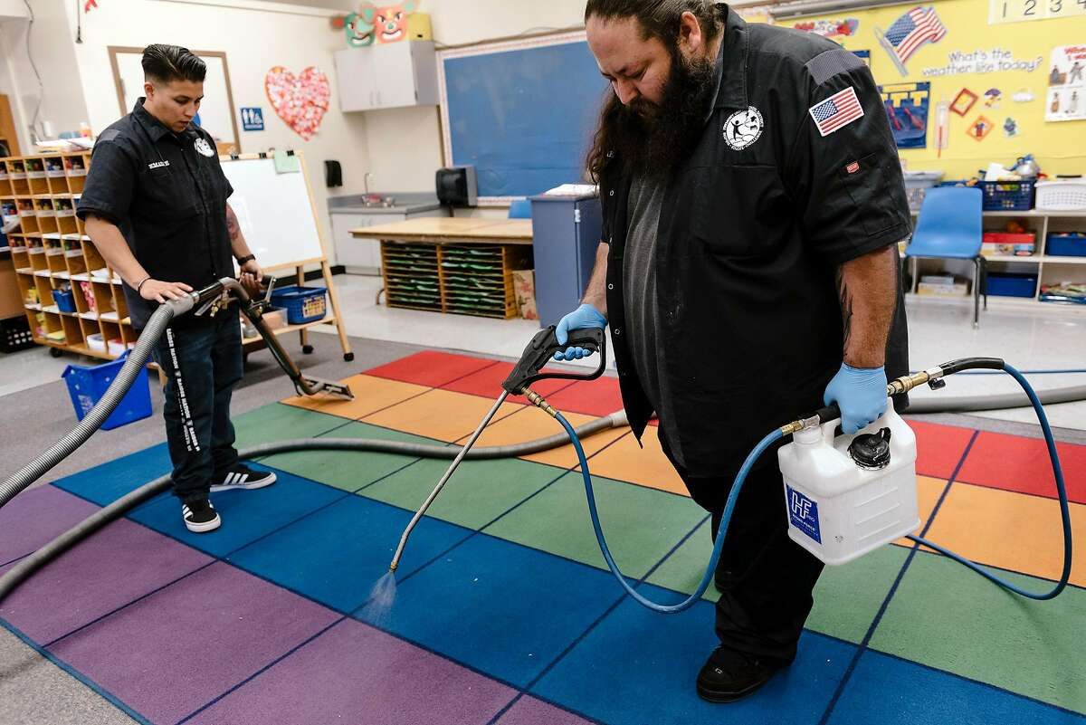 Fremont Unified School District mobile cleaning crew member Ken Sparks demonstrates spraying disinfectant before fellow crew member Emalee Herrera uses a steam cleaner on a carpet in a classroom at Joshua Chadbourne Elementary School in Fremont, California, on Tuesday, March 3, 2020.