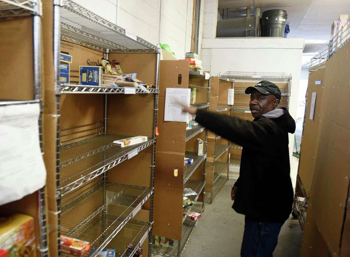 Warehouse Manager Willie Johnson chats beside a row of empty shelves at the Food Bank of Lower Farifield County in Stamford, Conn. Monday, March 9, 2020. Since the coronavirus outbreak, the food bank has experienced a shortage of food, particularly pasta, cereal and nonperishable canned goods.