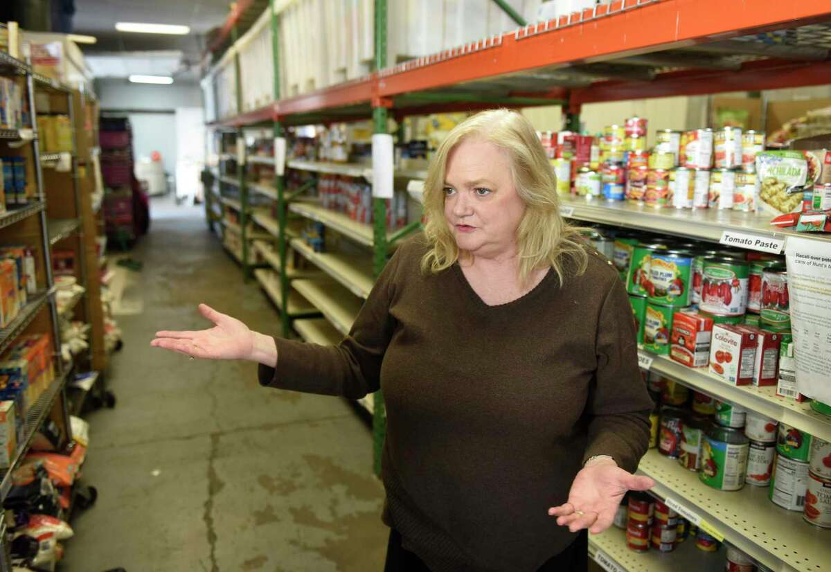 Executive Director Kate Lombardo chats beside a row of empty shelves at the Food Bank of Lower Farifield County in Stamford, Conn. Monday, March 9, 2020. Since the coronavirus outbreak, the food bank has experienced a shortage of food, particularly pasta, cereal and nonperishable canned goods.