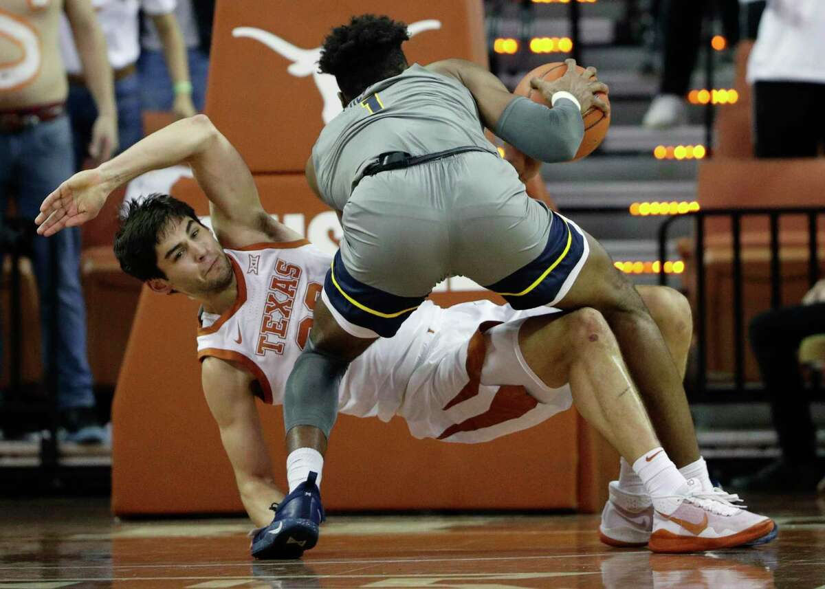 West Virginia forward Derek Culver (1) fouls Texas forward Brock Cunningham (30) as he drives to the basket during the second half of an NCAA college basketball game, Monday, Feb. 24, 2020, in Austin, Texas. (AP Photo/Eric Gay)