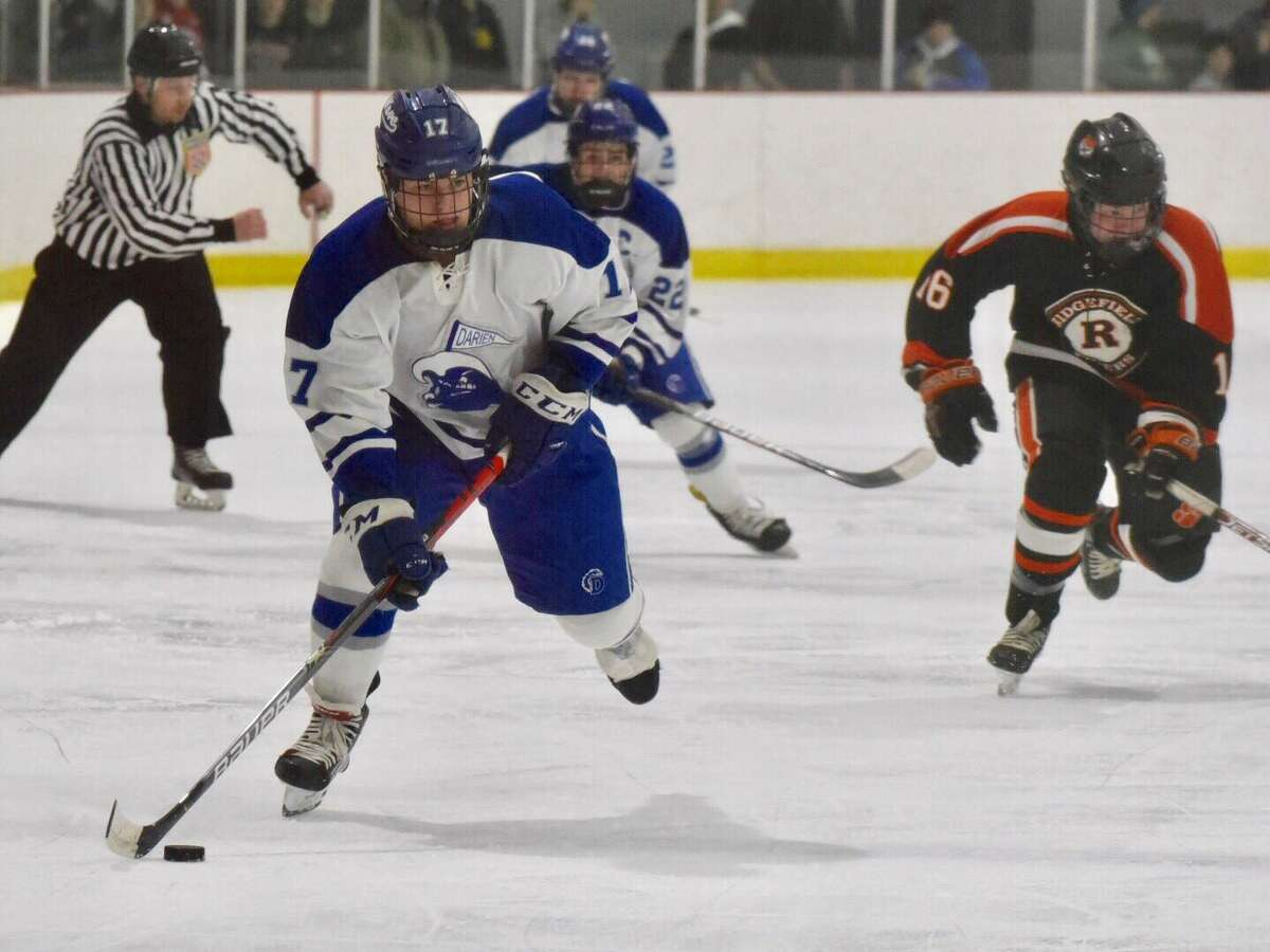 Darien's Jamison Moore (17) breaks out with the puck during a boys ice hockey game against Ridgefield at the Darien Ice House on Friday, Feb. 21, 2020.