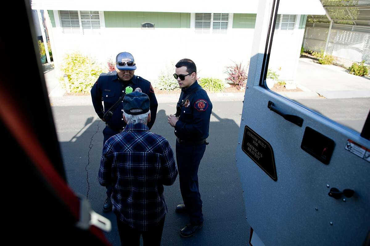 Firefighters Jaime Orozco and Kurt Seeberger (right) talk with Tom Kincaid about where he can charge his dead cell phone (at the fire station) during a routine tour by the fire department to check on communities effect by PG&E power cuts, Calistoga, California, October 11th, 2019. When the electricity is shut off, fire chief Steve Campbell says the fire department does hourly patrols around the neighborhoods effected. This senior also said she was on her way to the fairgrounds to plug her sleep apnea machine in - to get a nap. Power shutoff instituted by PG&E because potential