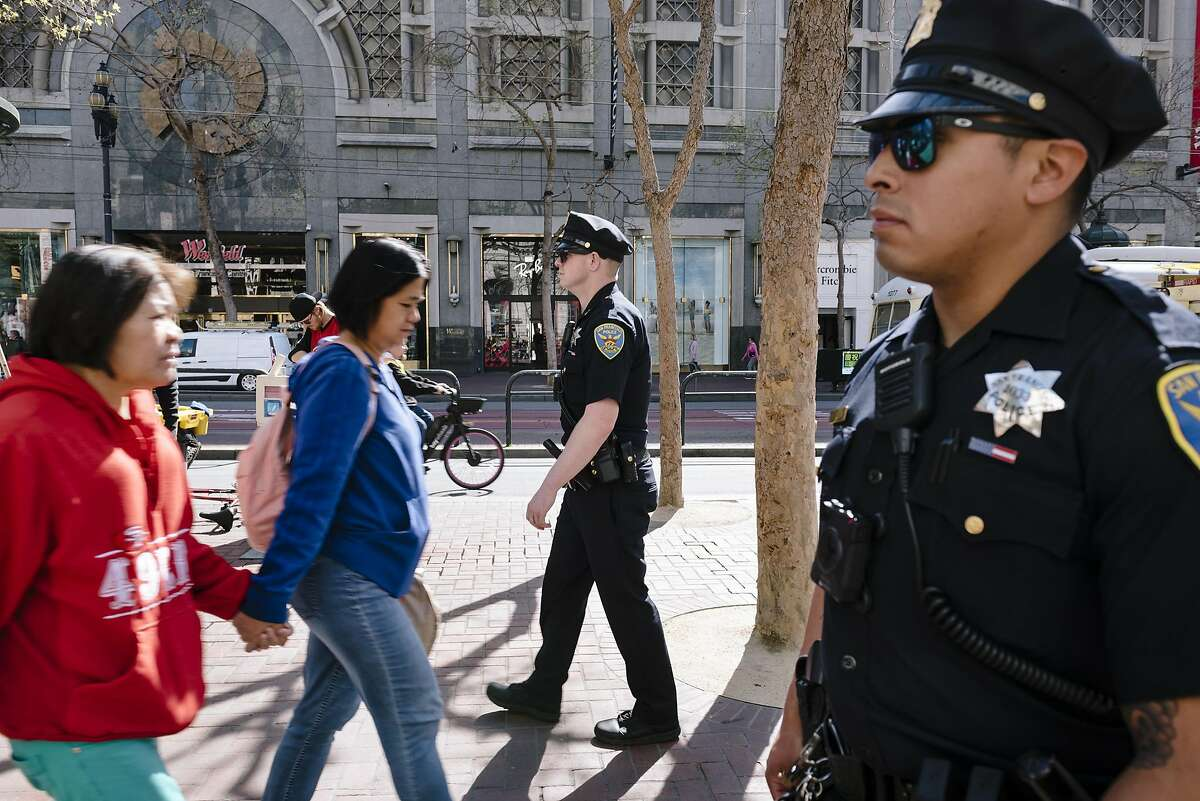 San Francisco Police Officers Cory McDowell, left, and Nick Parkin walk their beat on Market Street in San Francisco, California, on Wednesday, March 4, 2020.