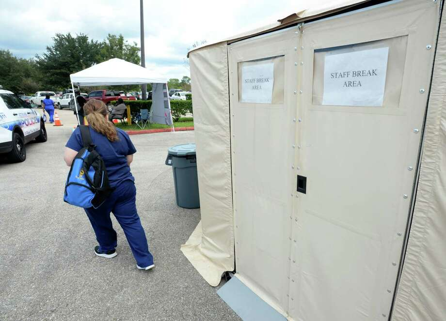 A Veterans' Affairs employee enters a tent being temporarily used as a break room at the Organization's Beaumont office Friday. Several mobile units and military tents are being used to treat patients until the building is renovated from Tropical Depression flooding. Repairs are expected to take months. Photo taken Friday, 9/27/19 Photo: Guiseppe Barranco/The Enterprise, Photo Editor / Guiseppe Barranco ©