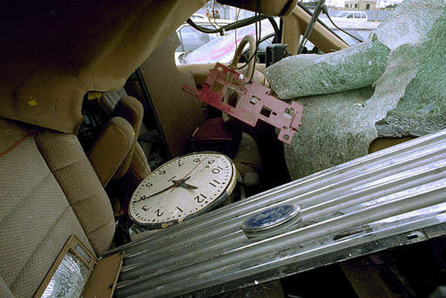 A clock, which reflects the time of the blast at the World Trade Center, sits in the wreckage of a vehicle at an impound lot in Brooklyn, March 9, 1993. Drivers who parked at the World Trade Center on the day of the bombing were allowed to pick up their vehicles, or at least what was left of them. (AP Photo/Kevin Larkin)