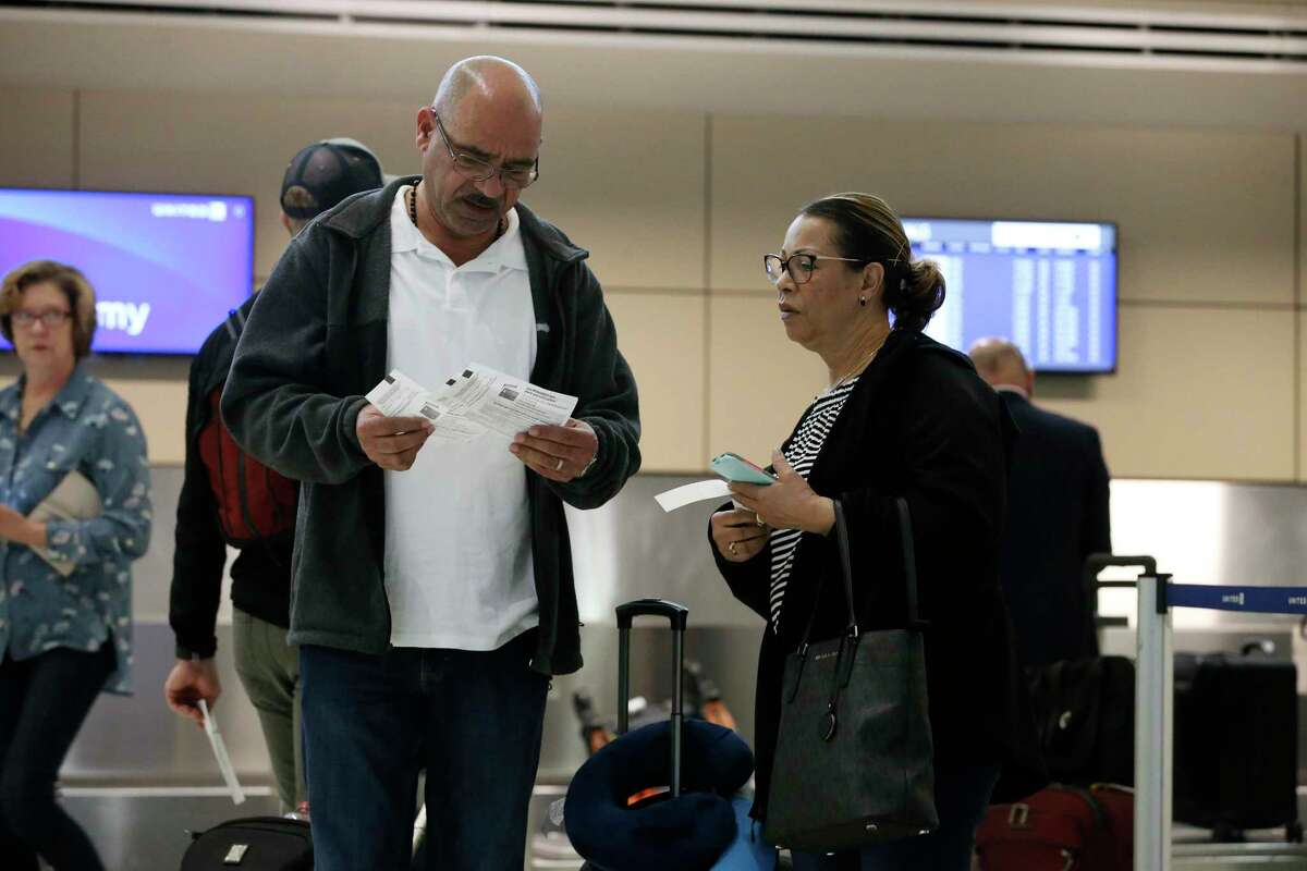 Andres Batista and Ana Pena check their boarding passes after checking in at the United Airlines ticket counter of the San Antonio International Airport, Monday, March 9, 2020. The couple was in San Antonio over the weekend to attend their granddaughter?•s air force basic training graduation ceremony. They were flying back to New Jersey.