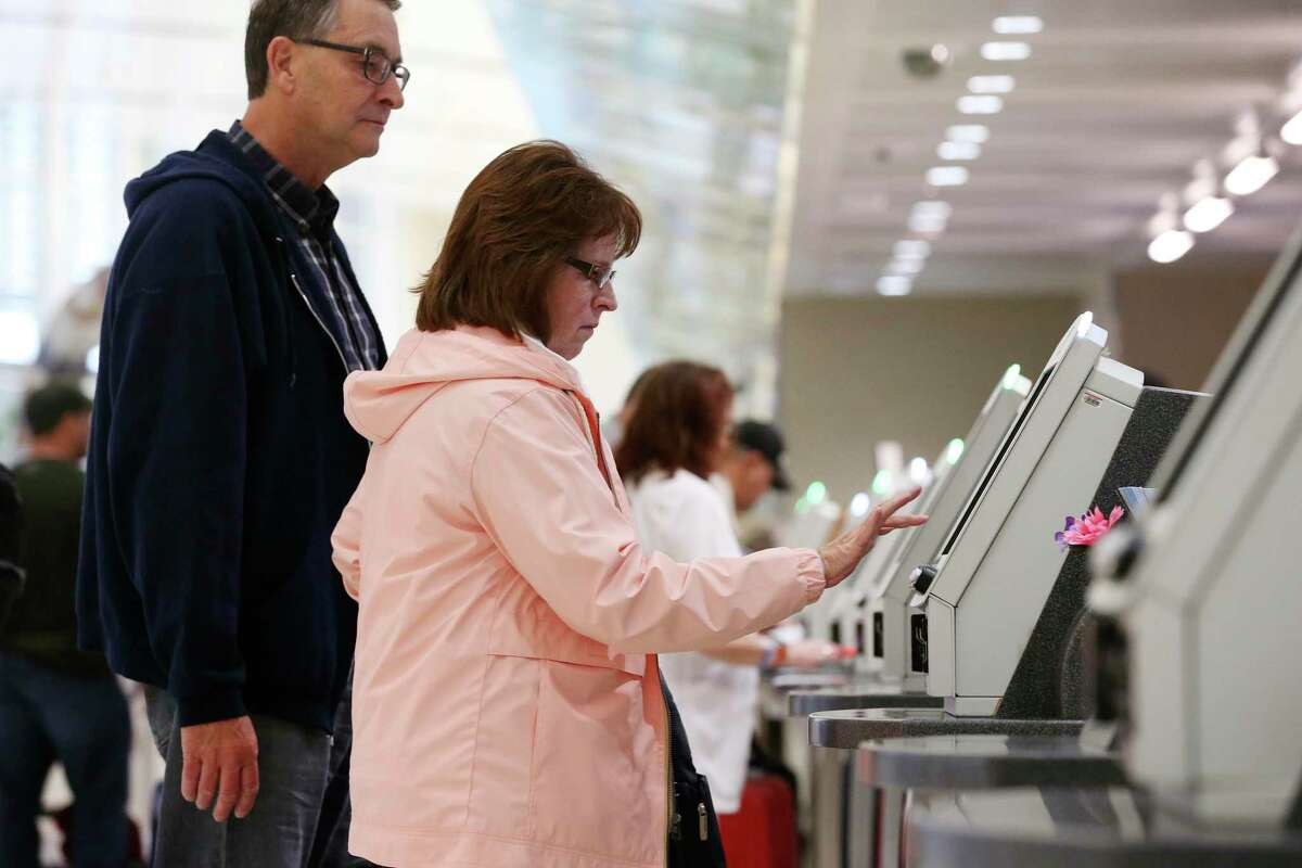 Lavell and Allyson Christensen check in at the United Airlines ticket counter at the San Antonio International Airport, Monday, March 9, 2020. The couple was flying back to St. George, Utah after spending the weekend in San Antonio.