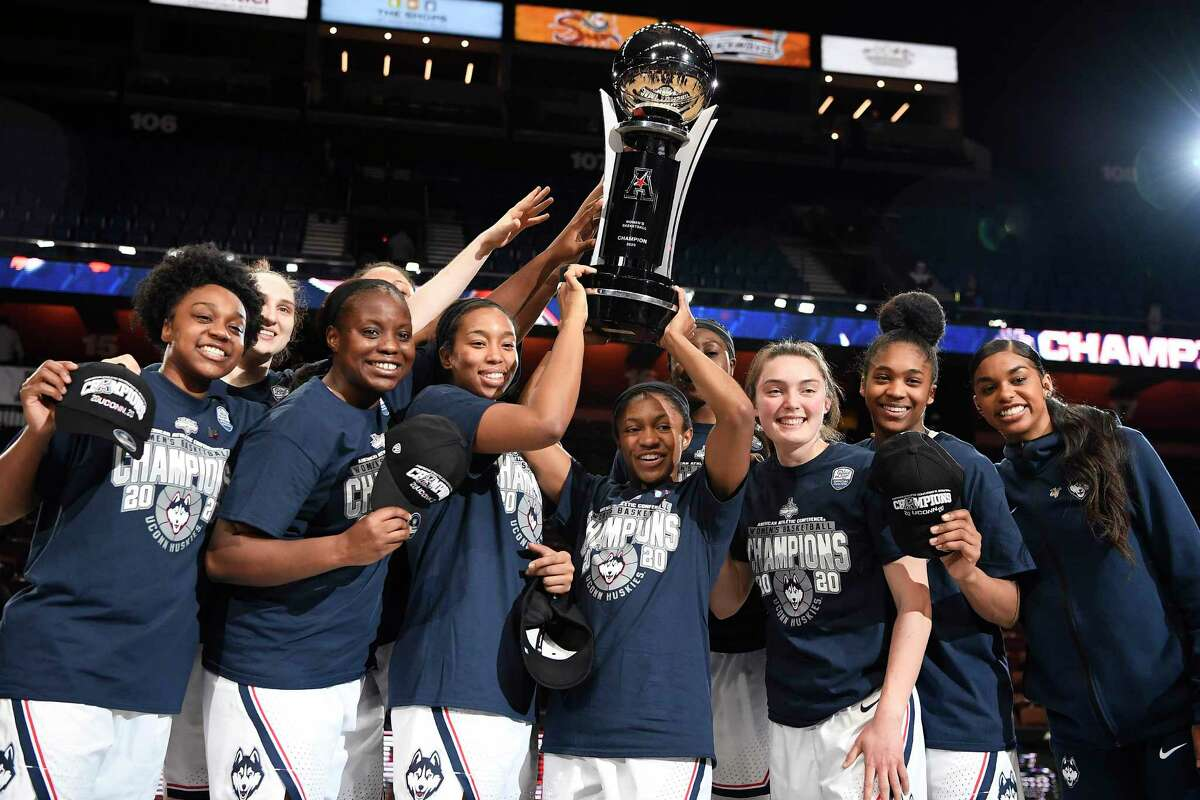 UConn players hold up the American Athletic Conference championship trophy the end of an NCAA college basketball game against Cincinnati in the American Athletic Conference tournament finals at Mohegan Sun Arena, Monday, March 9, 2020, in Uncasville.