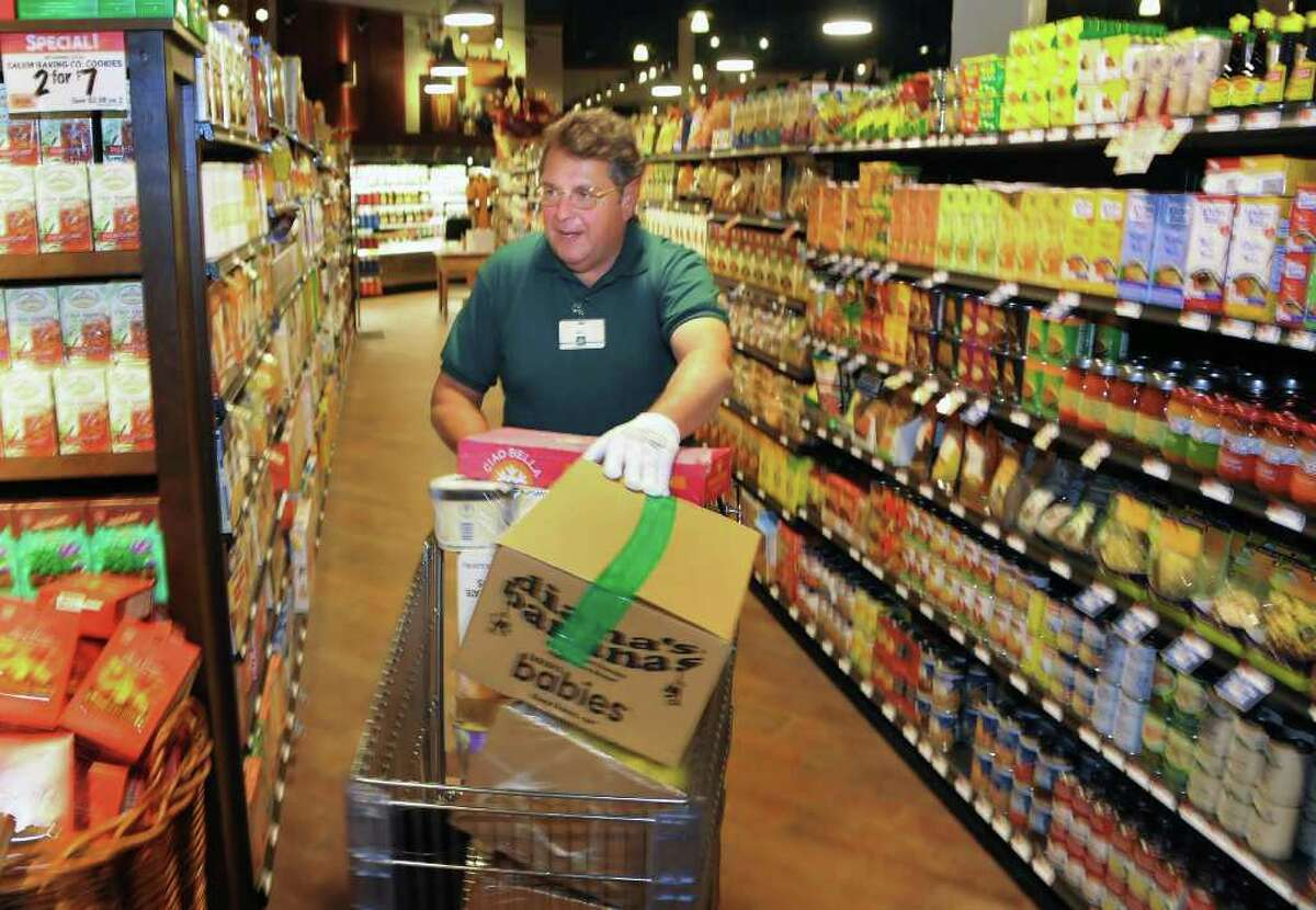 The Fresh Market's Bill Kouzan rushes ice cream through the aisles Tuesday afternoon in preparation for the Latham store's grand opening Wednesday. (John Carl D'Annibale / Times Union)