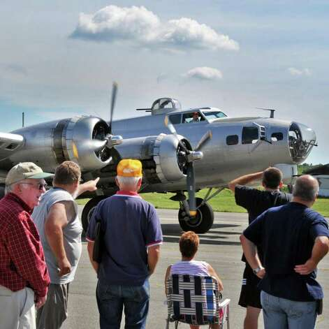 Aviation enthusiasts watch the WWII era B17 ?Aluminum Overcast?  taxi up to the Empire State Aerosciences Museum in Glenville Tuesday afternoon August 17, 2010. Operated by the Experimental Aircraft Association (EAA), the National tour of this aircraft helps people learn about the B17 and it?s important contribution to the outcome of World War 2. Some aircraft historians consider the B17 the most significant plane of WW II. Proceeds from the sale of rides and donations help the EAA keep the ?Aluminum Overcast? operating in top condition as flying museum. This is one stop in a national tour which began in the spring.    (John Carl D'Annibale / Times Union) Photo: John Carl D'Annibale / 00009894A