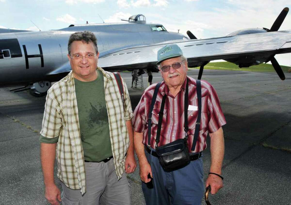 Aviation enthusiasts Dean Betz, left, of Houston, and his father Bob Betz of Rochester pose for a photo on their way for a ride aboard the WWII-era B17 ?Aluminum Overcast? at the Empire State Aerosciences Museum in Glenville on Tuesday, Aug. 17. Operated by the Experimental Aircraft Association, the National tour of this aircraft helps people learn about the B17 and its important contribution to the outcome of World War II. Proceeds from the sale of rides and donations help the EAA keep the ?Aluminum Overcast? operating in top condition as flying museum. (John Carl D'Annibale / Times Union)