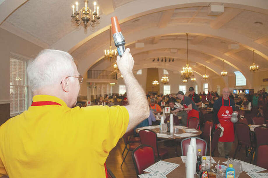 Kiwanis member Forrest G. Keaton uses his trusty, taped-up beacon Monday to let people know where seats are available during the club's Pancake & Sausage Day. The annual event raises money for the civic group's community and children's programs. Photo: Darren Iozia | Journal-Courier