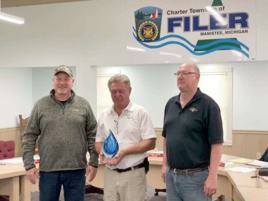 Mike Hiller (left), FilerTownship water operator, and Tom Stege (right), Filer Township treasurer, receive the award from Brian Minor, of the Michigan Rural Water Association. Photo: Courtesy Photo/Terry Walker