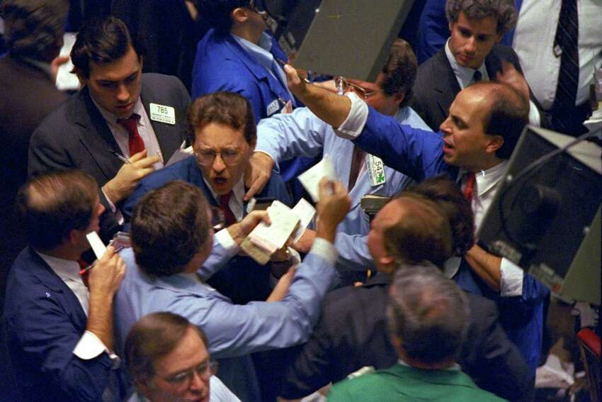 Traders on the floor of the New York Stock Exchange work frantically as panic selling swept Wall Street, Monday, October 19, 1987. The Dow Jones Industrial average plunged more than 500 points for the biggest one-day loss in history. (AP Photo/Peter Morgan)