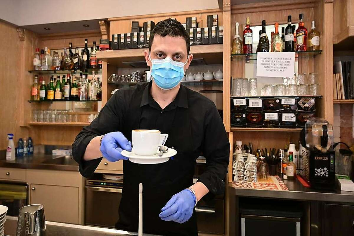 A waiter wearing a respiratory mask as part of precautiobary measures against the spread of the new COVID-19 coronavirus, hands a capuccino at a cafe in downtown Milan on March 10, 2020.