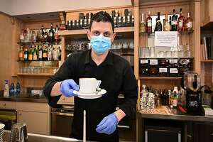 A waiter wearing a respiratory mask as part of precautiobary measures against the spread of the new COVID-19 coronavirus, hands a capuccino at a cafe in downtown Milan on March 10, 2020. - Italy imposed unprecedented national restrictions on its 60 million people on March 10, 2020 to control the deadly coronavirus, as China signalled major progress in its own battle against the global epidemic. (Photo by MIGUEL MEDINA / AFP) (Photo by MIGUEL MEDINA/AFP via Getty Images)