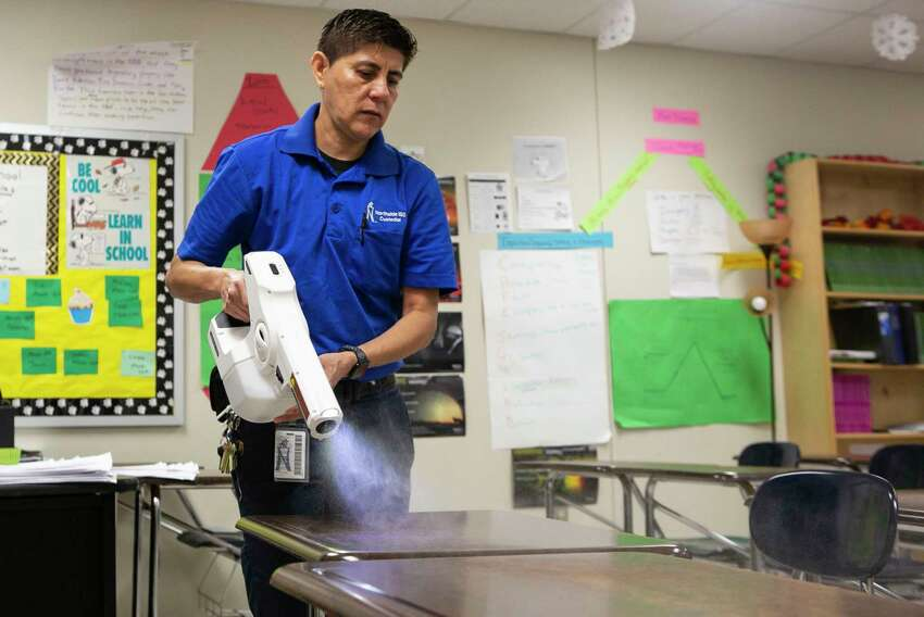 Head Campus Custodian Patricia Avila uses an electrostatic sprayer to clean classrooms of Dolph Briscoe Middle School in San Antonio, Texas, March 9, 2020. Northside ISD Superintendent Brian Woods sent a letter to parents about coronavirus and Spring Break informing parents that while the students are gone, extra cleaning will be done in classrooms.