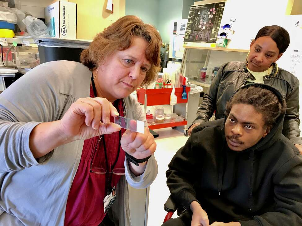 Lab manager Susan Goderie shows a glass slide with stem cells and antibodies to gunshot victim Ellazar Williams, 20, who was left paralyzed from the chest down, at the New York Neural Stem Cell Institute in Rensselaer.