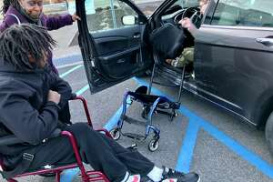 Ellazar Williams and Alice Green look on as Otto Miller demonstrates his fluid movement of transferring from his wheelchair into his hand-controlled Chrysler 200 sedan/