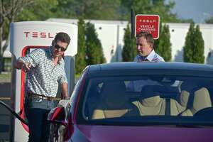 Phil Levieff, of Fairfield, left, demonstrates the ability of his Tesla model S to park itself to Adam Wood, of Rocky Hill, at Danbury Fair Mall on July 26, 2018.