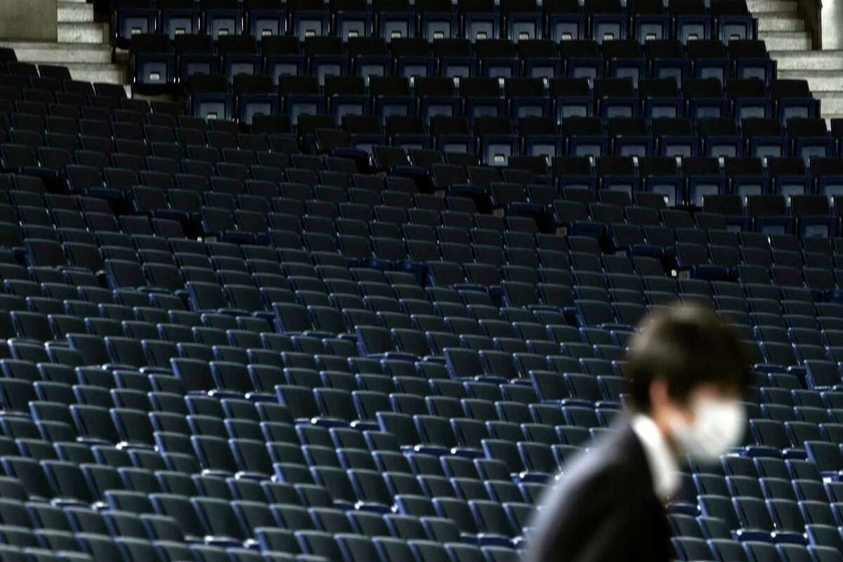 A staff walks spectators' stands being empty during a preseason baseball game between the Yomiuri Giants and the Yakult Swallows at Tokyo Dome in Tokyo Saturday, Feb. 29, 2020. Japan's professional baseball league said it will play its 72 remaining preseason games in empty stadiums because of the threat of the spreading coronavirus.