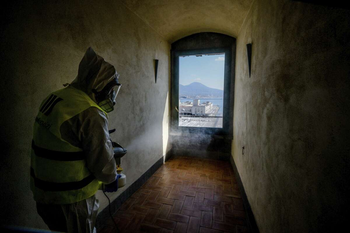 A worker sprays disinfectant as sanitization operations against Coronavirus are carried out in the museum hosted by the Maschio Angioino medieval castle, in Naples, Italy, Tuesday, March 10, 2020. (Alessandro Pone/LaPresse via AP)