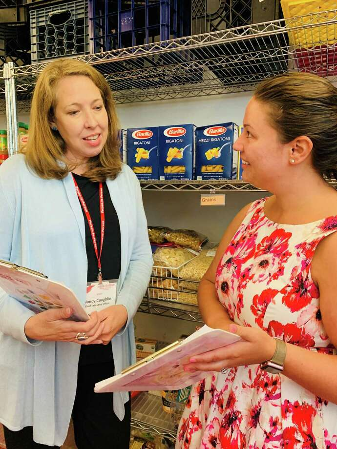 Nancy Coughlin, Person-to-Person CEO, and Marie Cartagena, Darien Site manager, review plans to ensure that their food pantries are stocked and prepared. Photo: Contributed Photo / Connecticut Post