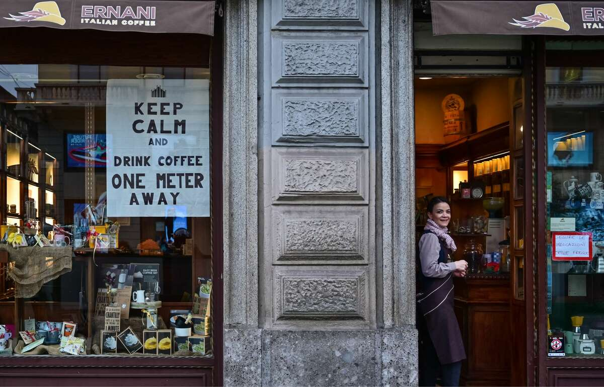 A waitress looks on by a sign advising clients to keep distance on a cafe's window on March 10, 2020 in downtown Milan. - Italy imposed unprecedented national restrictions on its 60 million people on March 10, 2020 to control the deadly coronavirus, as China signalled major progress in its own battle against the global epidemic. (Photo by MIGUEL MEDINA / AFP) (Photo by MIGUEL MEDINA/AFP via Getty Images)