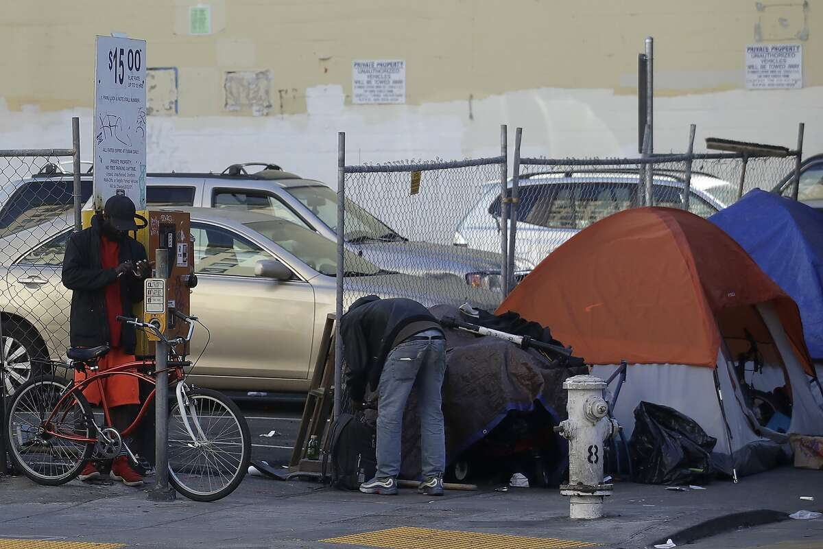 People stand in front of tents on a sidewalk in San Francisco, Tuesday, Feb. 18, 2020. (AP Photo/Jeff Chiu)