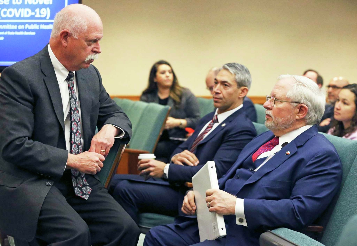 Houston public health authority Dr. David Persse, left, talks to Texas Department of Health Services Commissioner Dr. John Hellerstedt, right, during a Legislative hearing about the coronavirus threat on March 10. Listening to the conversation is San Antonio Mayor Ron Nirenberg.